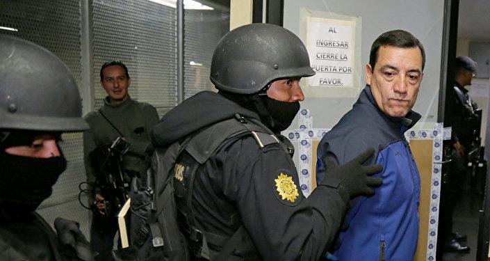 Policemen escort former Guatemalan Minister of Defense William Mansilla