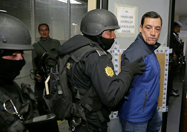 Policemen escort former Guatemalan Minister of Defense William Mansilla