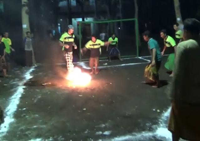 Un partido de fútbol con un coco incendiado