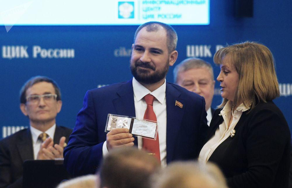 Maxim Suraikin muestra su certificado de registro como candidato presidencial