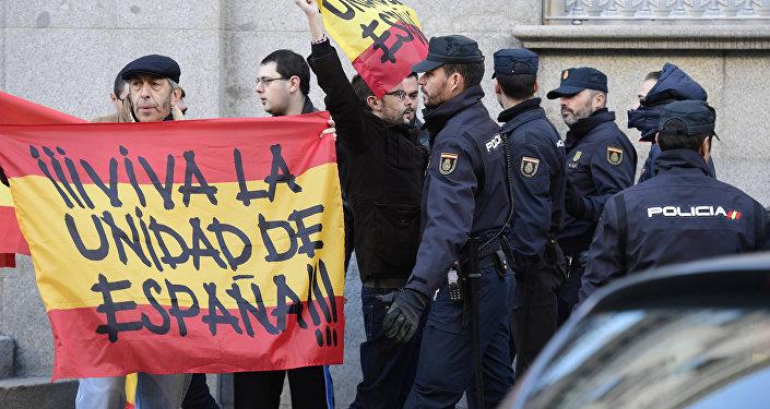 LLa policía española monta guardia junto a dos hombres con banderas españolas que dicen Viva la unidad de España