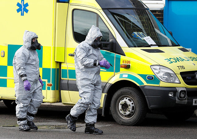Soldados con trajes de protección caminan al lado de una ambulancia, imagen referencial