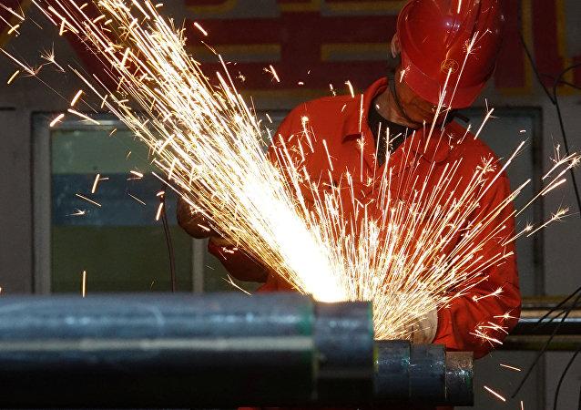 Un trabajador pule tubos de acero en una fábrica de Dongbei Special Steel Group en Dalian