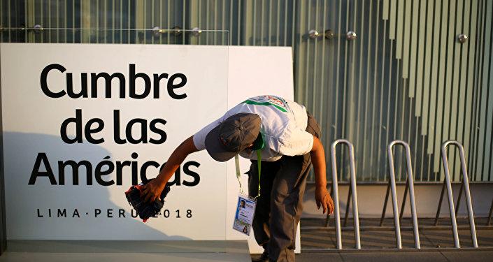 Una mujer limpia un cartel en la previa de la VIII Cumbre de las Américas en Lima, Perú.
