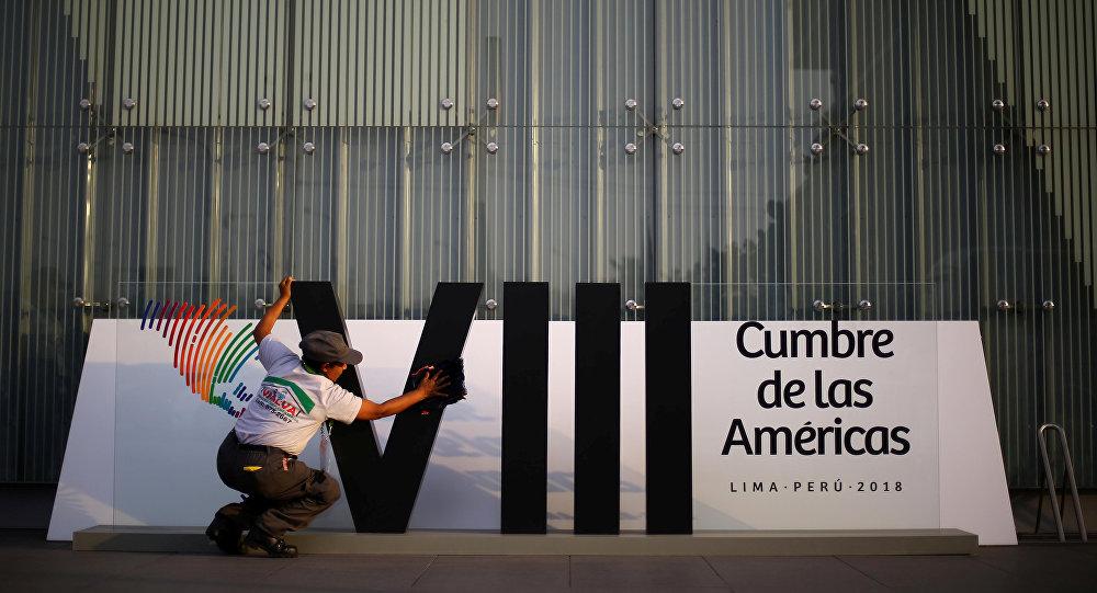 Una mujer limpia un cartel en la previa de la VIII Cumbre de las Américas en Lima, Perú