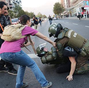 Un manifestante contra el bombardeo en Siria es reprimido en las afueras de la embajada de EEUU en Santiago de Chile.