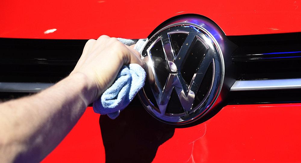 Un hombre puliendo el logotipo del automóvil del fabricante de automóviles alemán Volkswagen