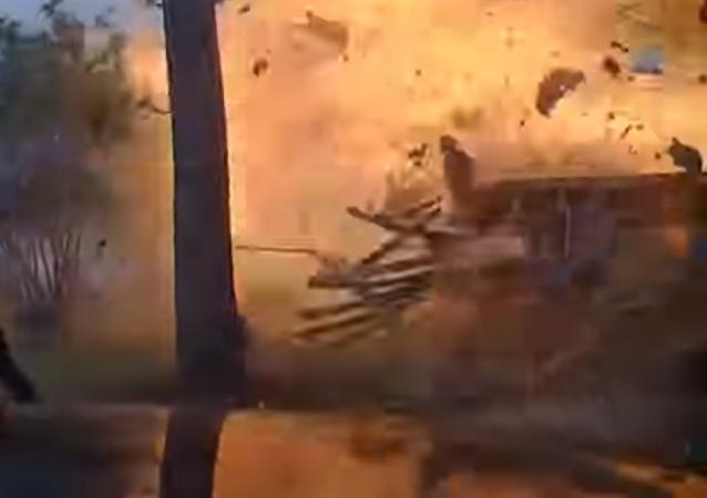 Una cámara capta el momento en el que un policía se acerca a una casa y esta explota