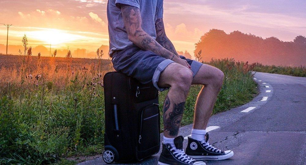 Un turista sentado sobre su equipaje