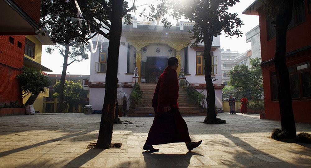 Un monje tibetano camina por un monasterio