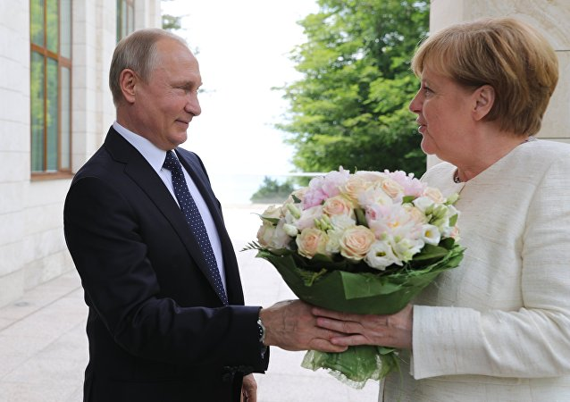 El presidente ruso Vladímir Putin regala flores a la canciller alemana, Angela Merkel