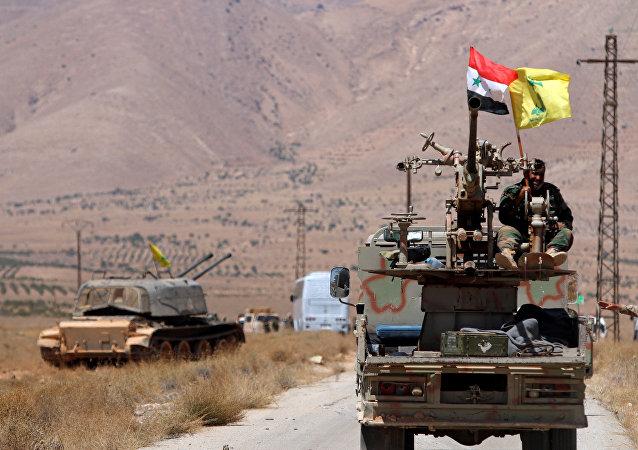 Un vehículo militar con las banderas de Siria e Hizbulá