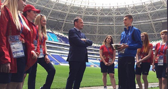 El presidente del Instituto Bering Bellingshausen para las Américas, Sergey Brilev, entrega el pasto del Estadio Centenario de Montevideo para el Cosmos Arena de Samara a la joven promesa del fútbol ruso Nikita Kotin