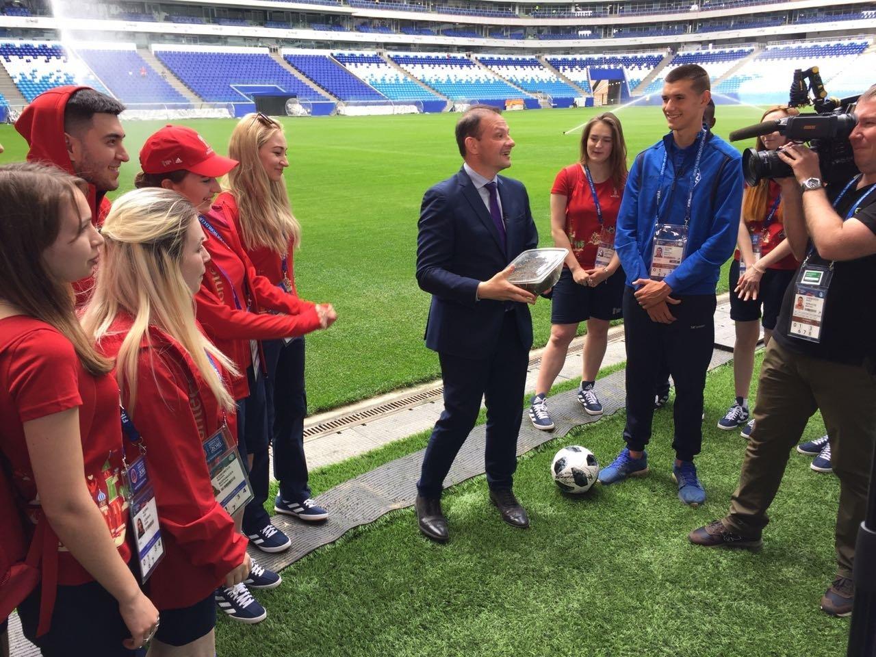 El presidente del Instituto Bering Bellingshausen para las Américas, Sergey Brilev, entrega a la joven promesa del fútbol ruso Nikita Kotin el pasto del Estadio Centenario de Montevideo para el Cosmos Arena de Samara.
