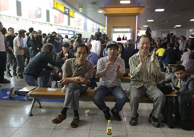 Surcoreanos observan en una pantalla de televisión la reunión entre Trump y Kim Jong-un