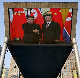 La pantalla muestra la reunión entre líder norcoreano, Kim Jong-un, y presidente chino, Xi Jinping, Pekín, China