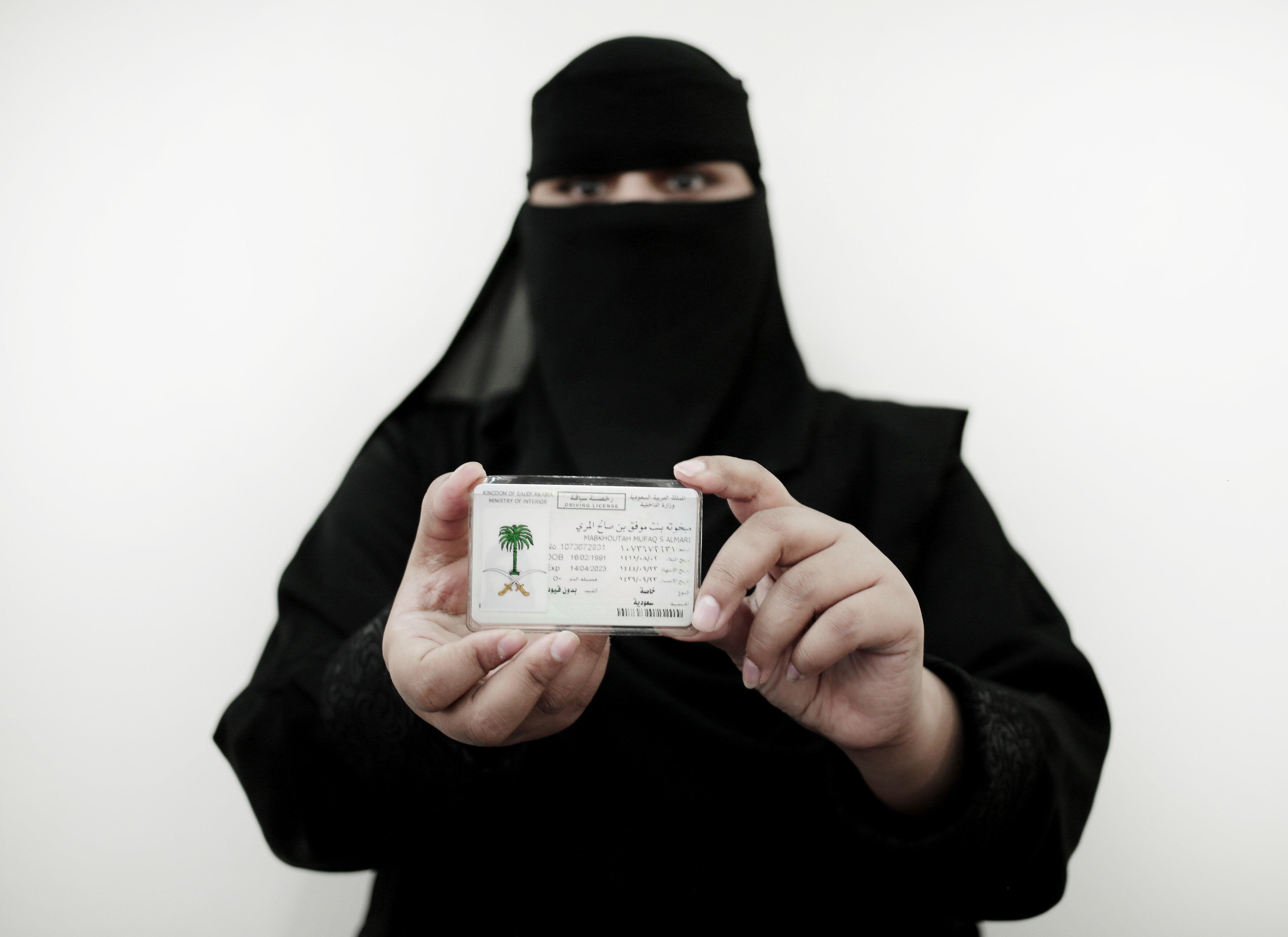 Una mujer saudí muestra su carnet de conducir