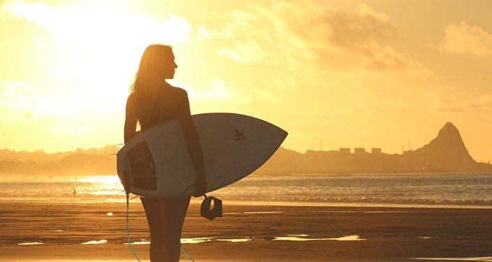 Una chica con una tabla de surf (imagen referencial)