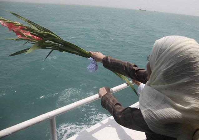 Una mujer iraní echa flores en el Golfo Pérsico durante una ceremonia que recuerda a los 290 pasajeros del vuelo 655 de Iran Air