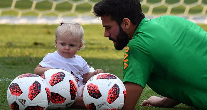 El arquero brasileño Alisson Becker y su hija Helena