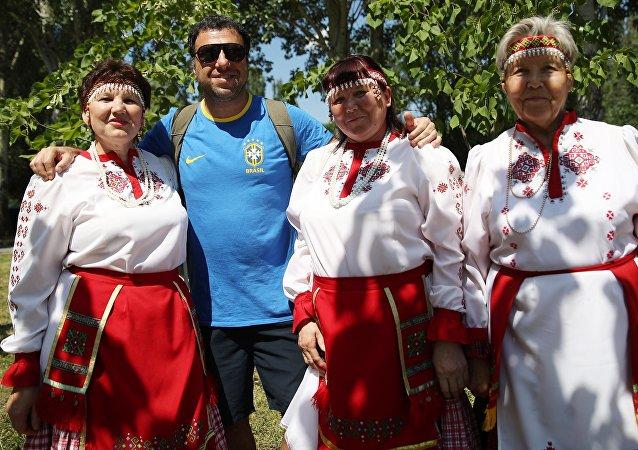 Un hincha brasileño se toma una foto con mujeres vestidas con atuendos típicos en la fiesta de Sabantuy, en Samara.