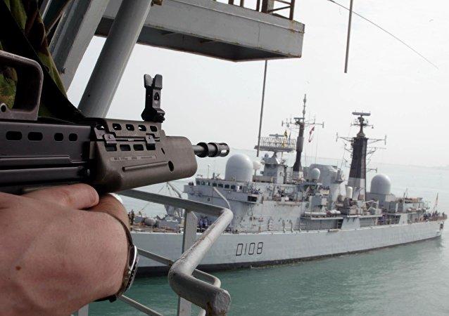 Un marine británico sobre el barco Diligence al lado del destructor Cardiff D108