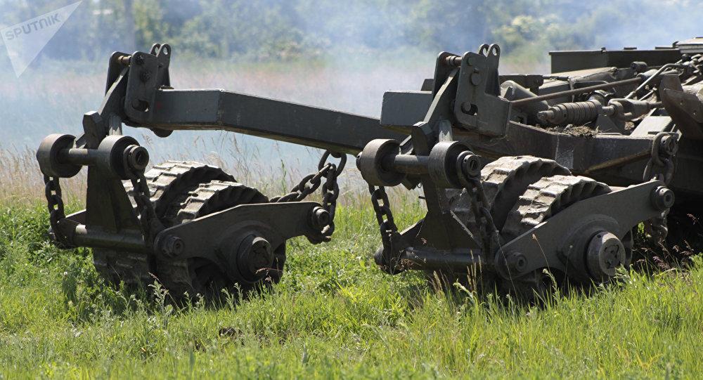 Una máquina dragaminas al lado de un tanque