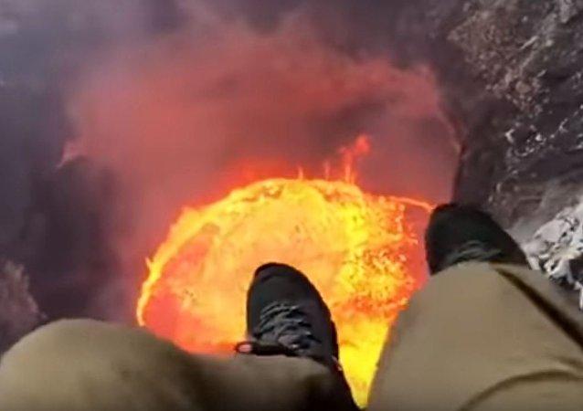 Hombre colgado sobre un volcán