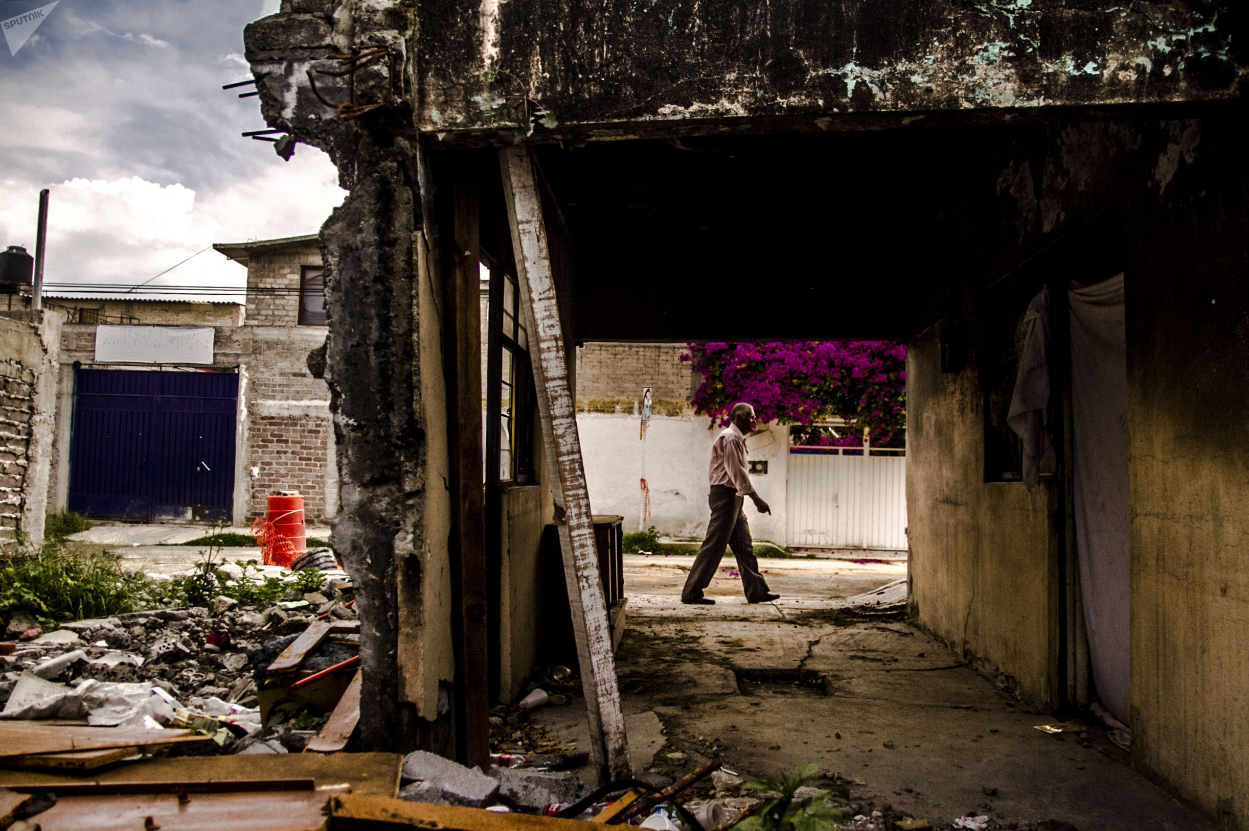 Juan Salgado camina frente a una de las casas dañadas en la Colonia del Mar, tras el sismo del 19 de septiembre de 2017.