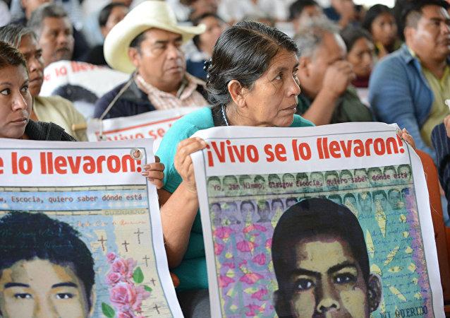 Personas sostienen carteles que recuerdan a los 43 desaparecidos de Ayotzinapa