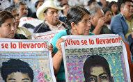 Personas sostienen carteles que recuerdan a los 43 desaparecidos de Ayotzinapa, en una visita de la Comisión Interamericana de Derechos Humanos a la escuela normal en la que estudiaban, en 2015.