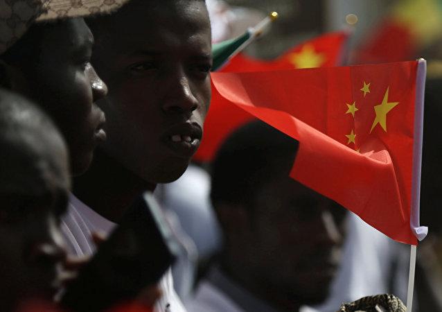 Los senegaleses reciben a la delegación china en el aeropuerto con las banderas de China en las manos