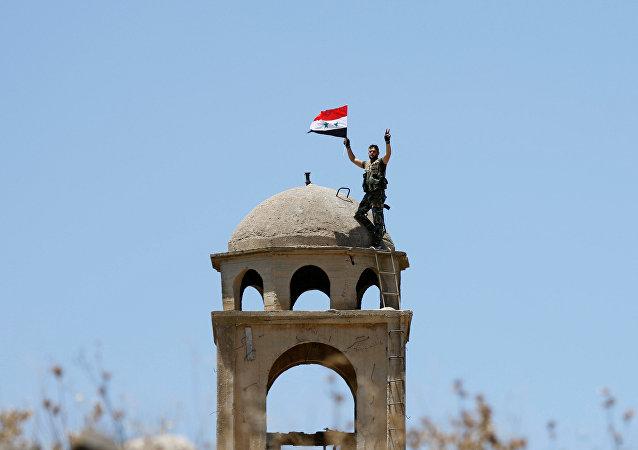 Un soldado sirio con su bandera
