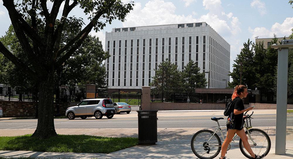 Una mujer empuja su bicicleta frente la Embajada de Rusia en Washington, EEUU, el 6 de agosto de 2018