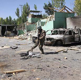 Un miembro de las fuerzas de seguridad afganas junto a vehículos dañados después de una explosión, Afganistán