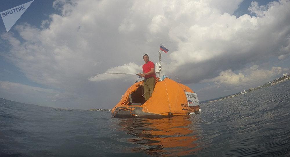 El viajero ruso Yuri Burlak con su barco