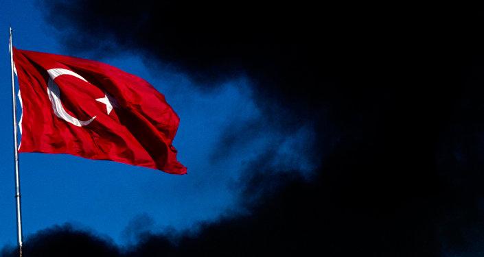 Una bandera turca alza en medio de humo