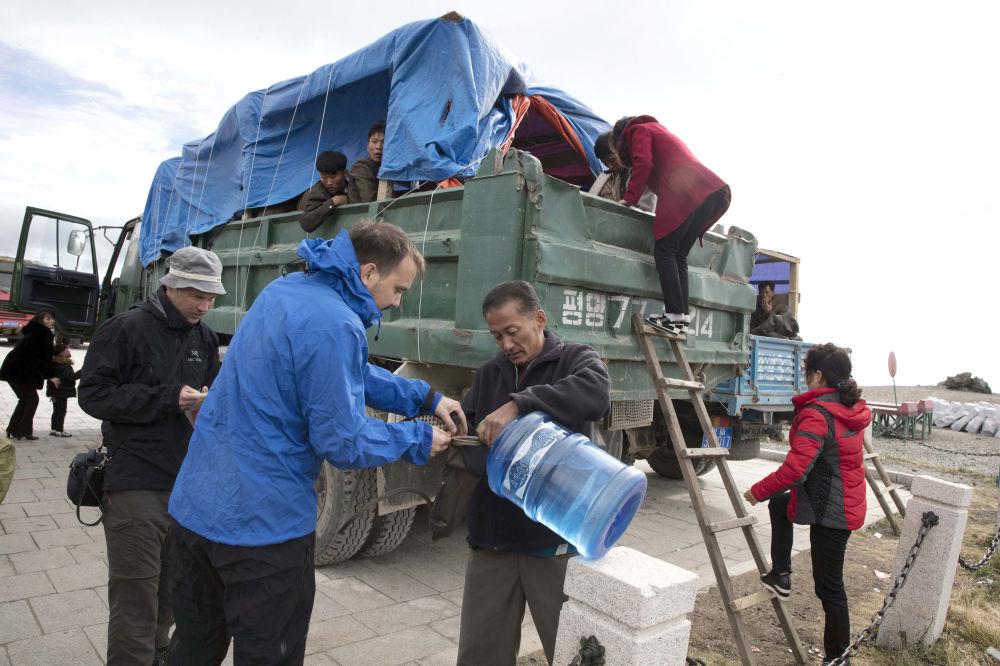 El grupo de turistas hace acopio de provisiones de camino al monte Paektu.