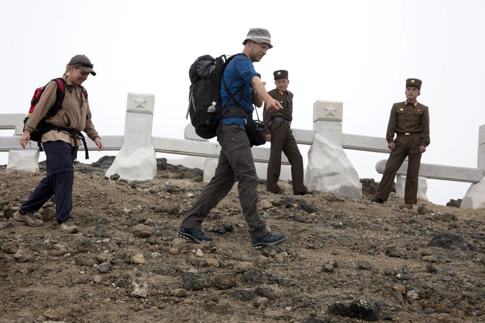 El grupo de turistas pasa al lado de unos soldados norcoreanos de camino al monte Paektu.