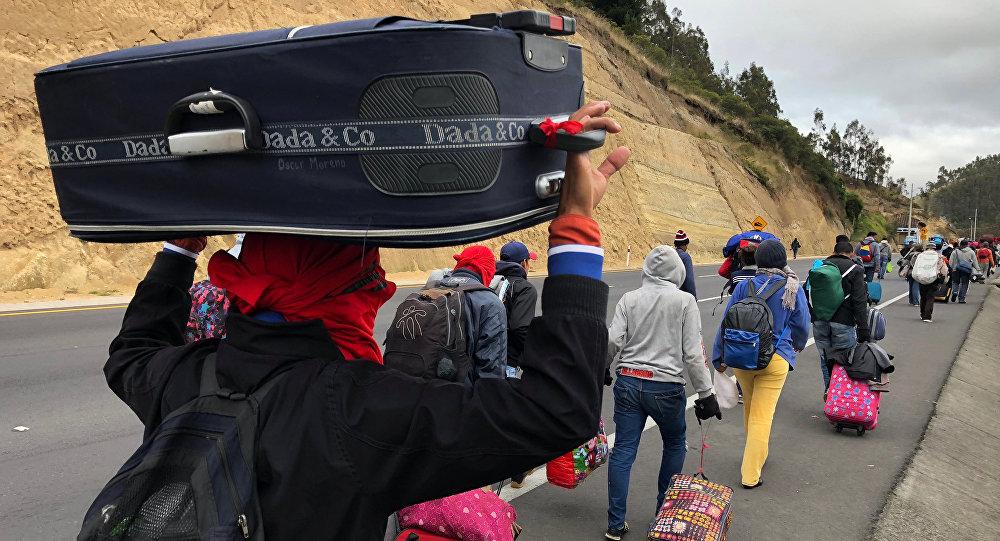 Los migrantes venezolanos caminan a lo largo de una carretera