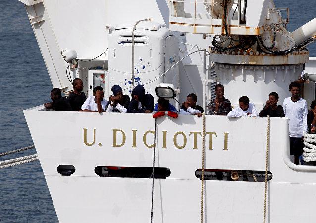 Los migrantes esperan para desembarcar del barco de la guardia costera italiana Diciotti cuando llegan al puerto de Catania, Italia