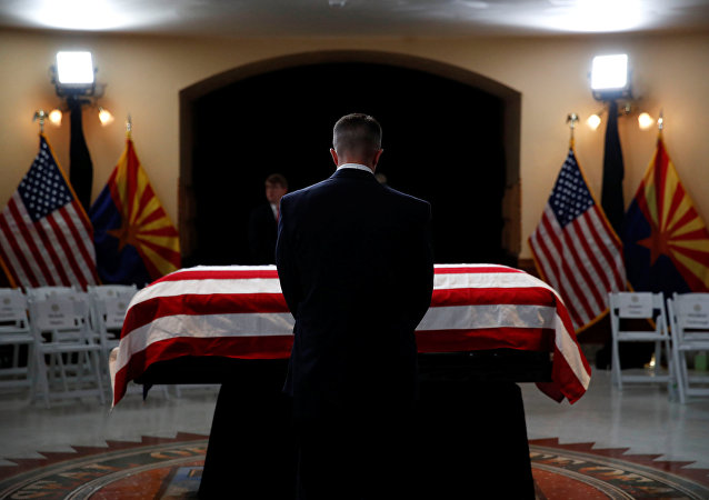 Una persona delante del ataúd del senador John McCain