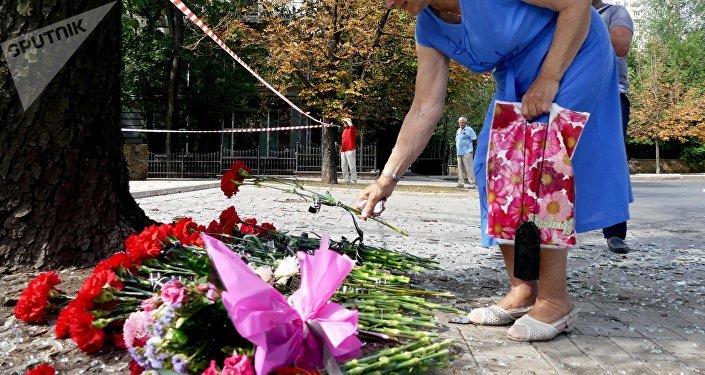 Mujer dejando una flor en santuario