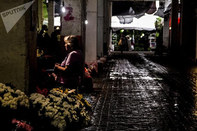 Una marchanta compra flores en el mercado Jamaica Vive