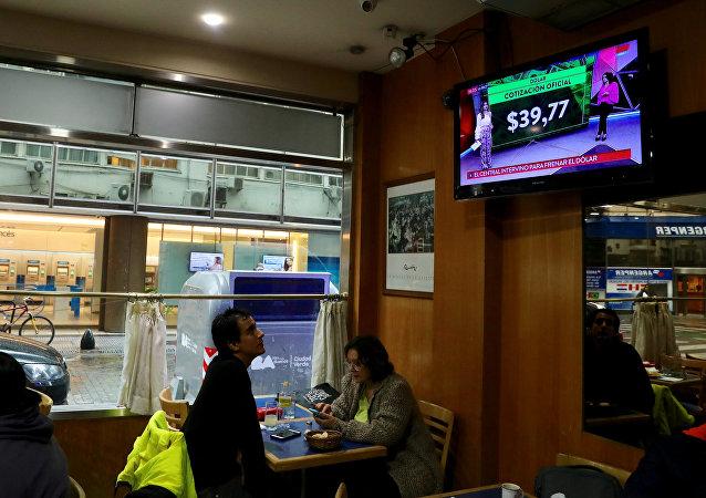 Un hombre ve por la TV las tasas de cambio del dólar en Buenos Aires, Argentina (archivo)