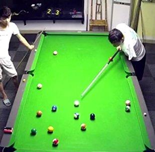 Hombre chino manco jugando el billar