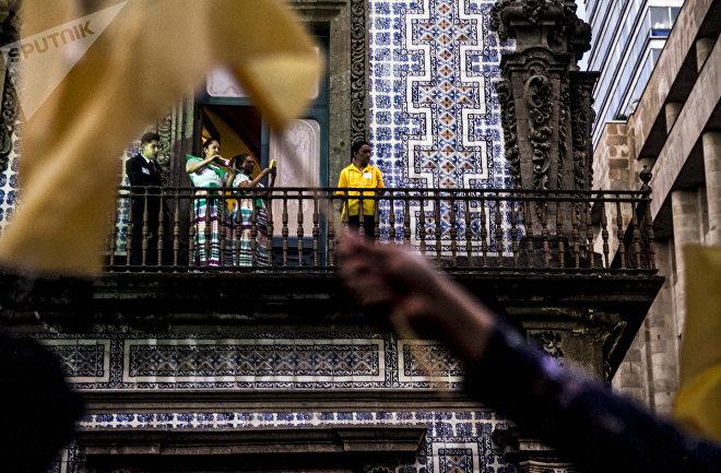 Trabajadores observan a los estudiantes que pasan con banderas de la UNAM durante la Marcha del Silencio 2018, en la Ciudad de México.