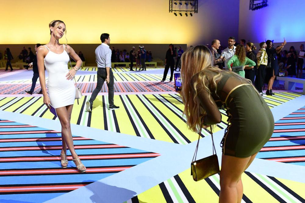 En Italia, a la moda se la considera una cuestión de Estado. En la foto, los asistentes a la muestra se hacen fotos justo antes de que las modelos comiencen a desfilar con la nueva colección de Versace.