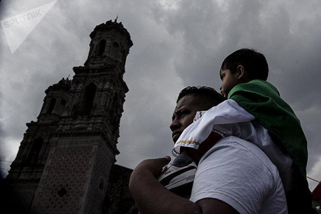 Padre carga a su hijo vestido como San Judas Tadeo frente al Templo de San Hipólito, en la Ciudad de México