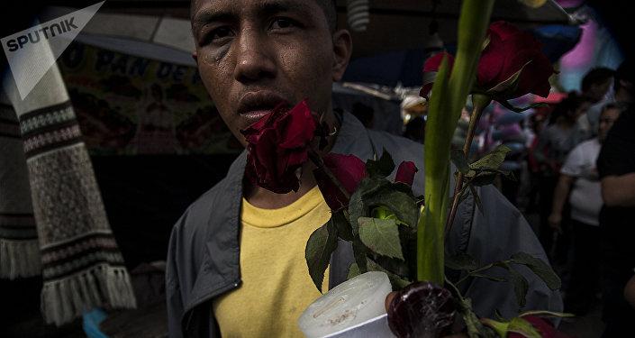 Hombre muestra los regalos recibidos por los demás fieles que reparten flores, dulces e imágenes